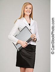 Beautiful blonde businesswoman holding laptop