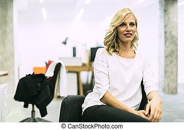Beautiful blonde businesswoman sitting in an office