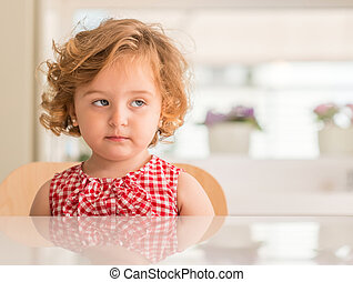 Beautiful blonde child unhappy with disgusting face at home.