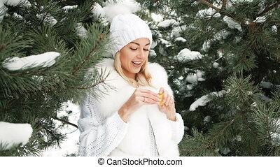 Beautiful blonde eats tangerine against background of winter landscape