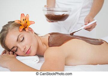 Beautiful blonde enjoying a chocolate beauty treatment at...