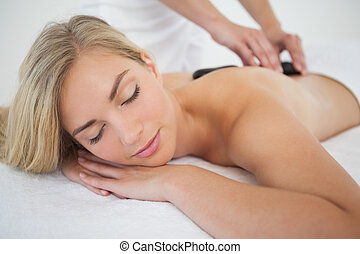 Beautiful blonde enjoying a hot stone massage at the health spa