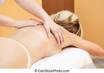Beautiful blonde enjoying a salt scrub treatment at the health spa