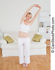 Beautiful blonde female stretching in the living room