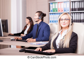 Beautiful blonde from customer support line in office working