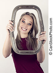 Beautiful blonde funny woman in red top holding a portrait frame in front of face