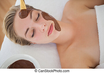 Beautiful blonde getting a chocolate facial treatment at the...