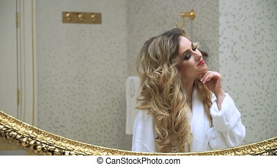 Beautiful blonde girl corrects her hair and looking in the mirror in her bathroom. Beauty young woman corrects her hair. Hairstyling