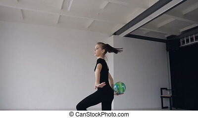 Beautiful blonde girl dressed in black sports body suit performs dancing with ball in gymnastics school. Gymnast with the ball in his hands doing acrobatic moves at sport indoor in the white background