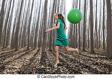 Beautiful blonde girl, dressed in green, jumping into the woods with a balloon in Fuente Vaqueros, Granada, Spain