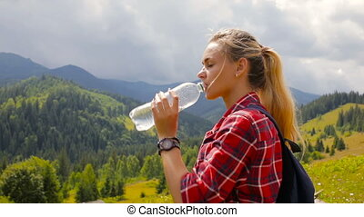 Beautiful blonde girl drinks water in the mountains
