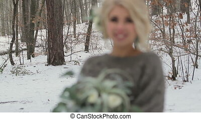 Beautiful Blonde Girl Holding a Bouquet in Winter Forest