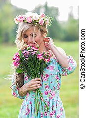 Beautiful blonde girl holding bouquet of flowers at the ...