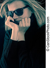 blonde girl in a black turtleneck with retro sunglasses