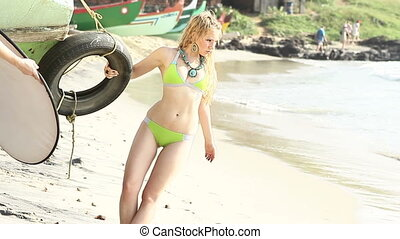 blonde girl in green swimsuit poses near boat on beach