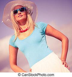 Beautiful blonde girl in hat on beach