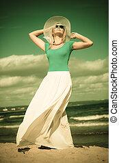 Beautiful blonde girl in hat on beach, summertime