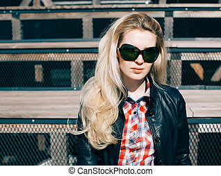 Beautiful blonde girl in huge sunglasses and a black jacket sitting on the steps of a sunny day