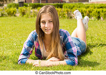 blonde girl in shirt lying on grass at sunny day