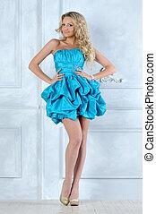 Beautiful blonde girl in short blue evening dress.