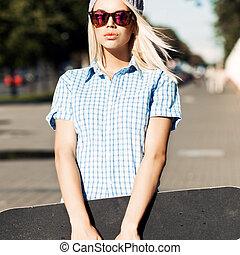Beautiful blonde girl in short shorts with skateboard - ...