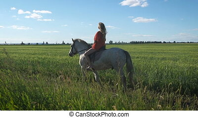 Beautiful blonde girl in the red shirt riding a horse at countryside