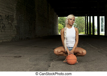 Beautiful blonde girl is sitting with basketball on the street