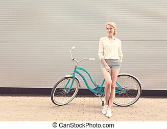 Beautiful blonde girl is standing near the vintage bicycle , warm, tonning