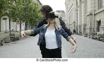 Beautiful blonde girl learning ballet moves in a street helped by her coach and a virtual reality headset vr