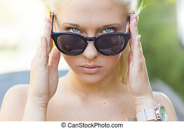 Beautiful blonde girl looking over her sunglasses -...