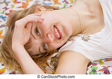 Beautiful blonde girl lying on the bed. Blanket with butterflies