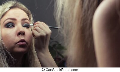 Beautiful blonde girl making evening make-up near the mirror