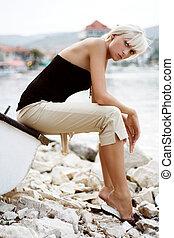 Beautiful blonde girl sitting at the lake