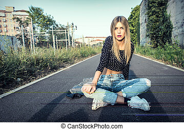 Beautiful blonde girl sitting on the street in town