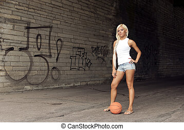 Beautiful blonde girl standing with basketball in the street