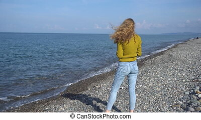 Beautiful blonde girl throws stones into the Black Sea,...