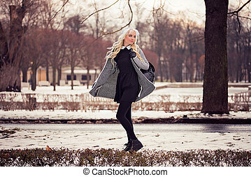 Beautiful blonde girl walking on the street