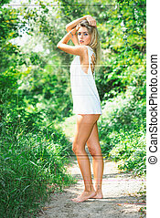 Beautiful blonde girl wild-style barefoot in the jungle