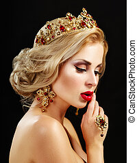 Beautiful blonde girl with a golden crown, earrings and professional evening make-up