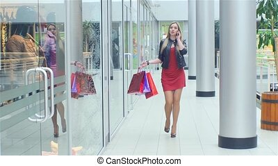 Beautiful blonde goes to store and talking on the phone. Close  up. Slow motion