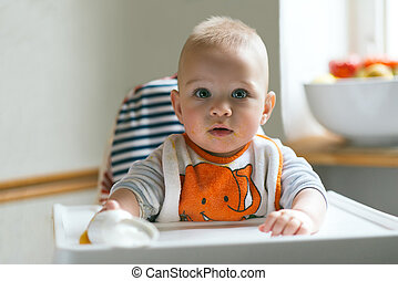 Beautiful blonde hair baby sitting in a high chair