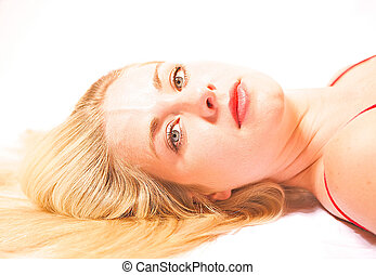 Beautiful blonde haired woman laying on her side.