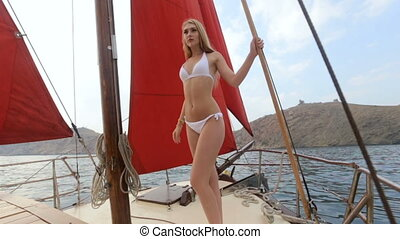 Beautiful blonde in a white bikini relaxing on a yacht at sea