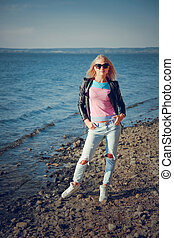 Beautiful blonde in ripped jeans posing on the shore of the ...