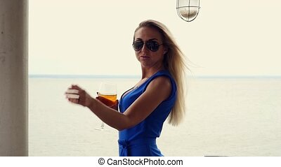 beautiful blonde is drinking white wine from a glass goblet,...