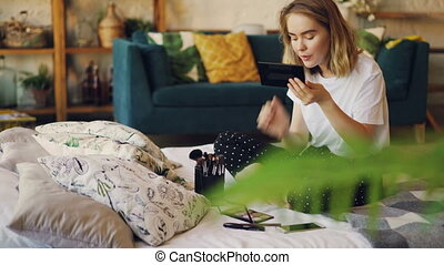 Beautiful blonde is painting lips putting on make-up using...