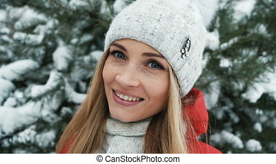 Beautiful blonde is smiling on background of winter landscape