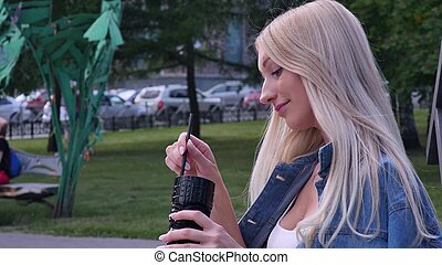 Beautiful blonde is talking on the phone during a lunch in a cafe. She smiles. Young woman with a smartphone in her hands in a summer cafe.