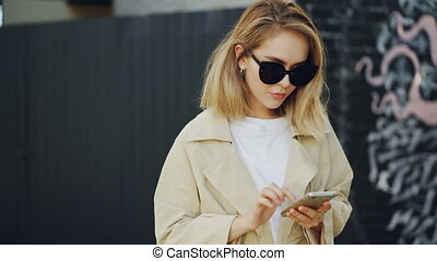 Beautiful blonde is using smartphone touching screen standing outdoors with graffiti on wall in background. Young woman is wearing sunglasses and summer coat.