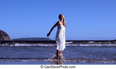 Beautiful blonde leaping up in white dress on sunny day at...
